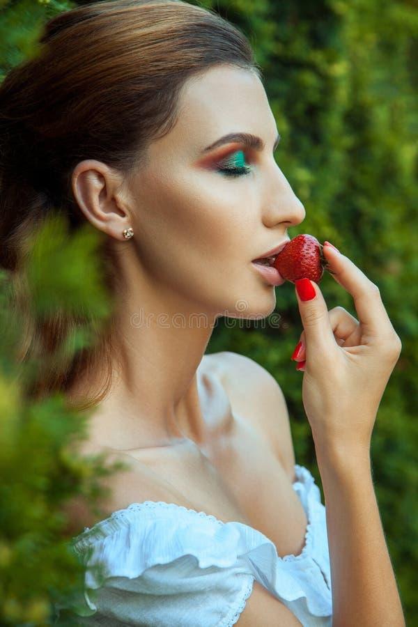 年轻妇女结束了眼睛和吃红色甜草莓 免版税库存图片