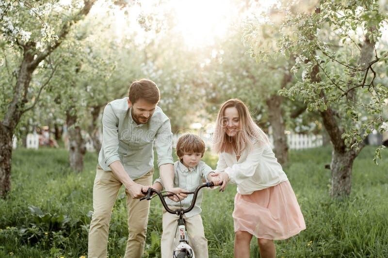 年轻妈妈和爸爸教他们的儿子骑自行车 免版税库存图片
