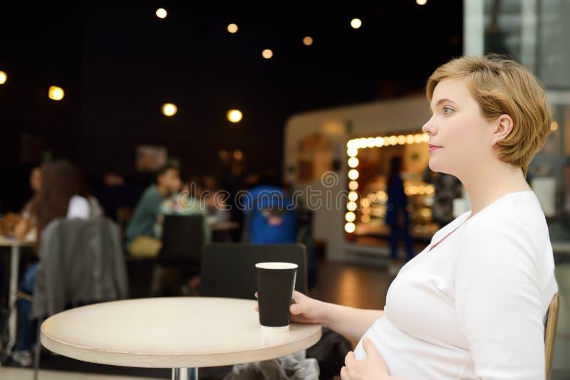 年轻孕妇休息的和饮用的咖啡在咖啡馆桌上在购物中心 在怀孕期间的营养 免版税图库摄影