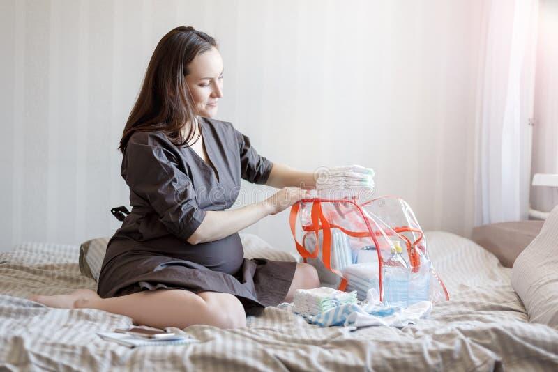 年轻孕妇折叠新生儿的尿布医院的一个袋子的 免版税库存图片