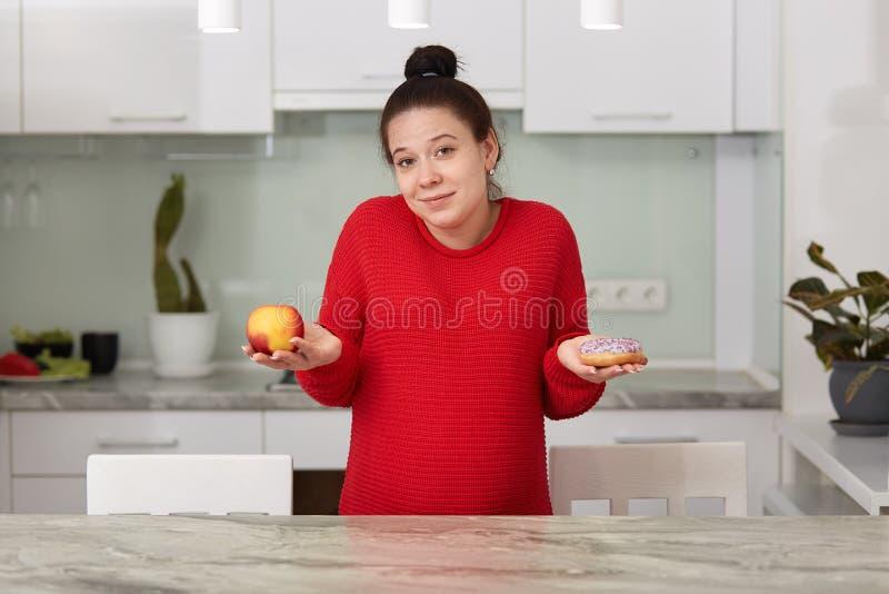 年轻孕妇用苹果和鲜美蛋糕室内射击在她的手上,在房子里决定怎样吃,有吸引力女性摆在 库存照片