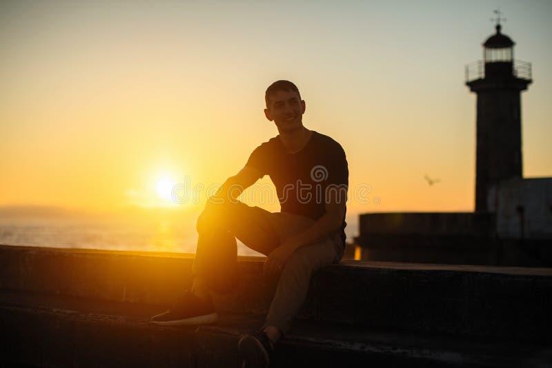 年轻孤立人坐在日落的海边散步 免版税库存图片