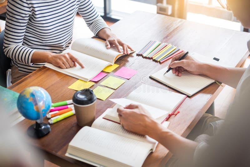 年轻学生同学在图书馆、教育和学校概念里帮助朋友追赶的作业簿和学习辅导 库存照片