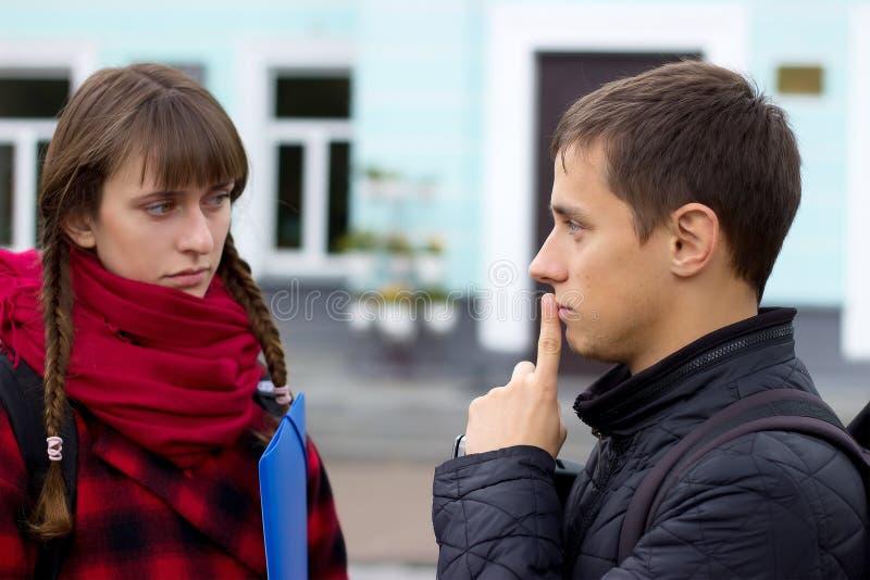 年轻学生朋友谈话在学院 证明某事的女孩尝试指向手指 图库摄影