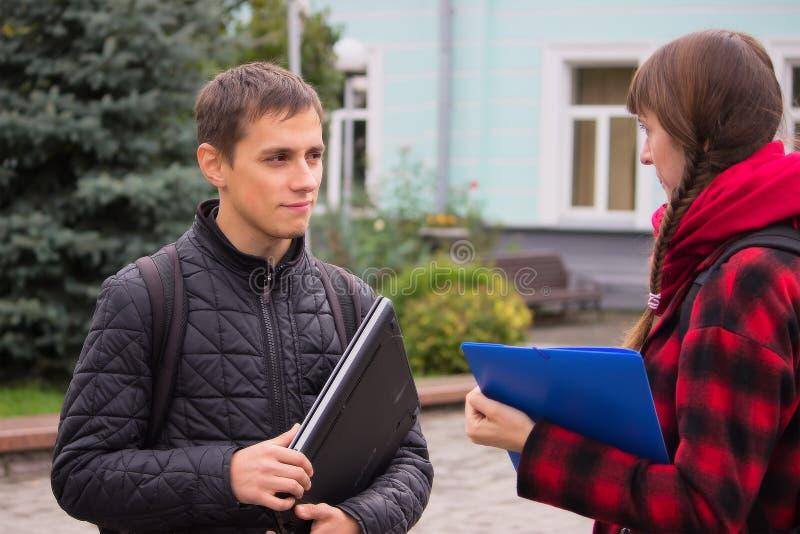 年轻学生朋友谈话在学院 图库摄影