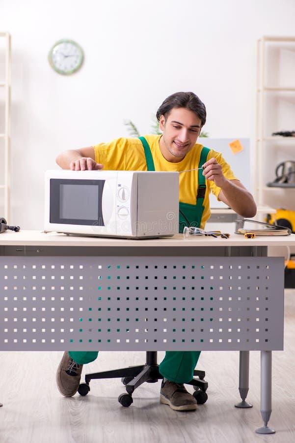 年轻安装工在服务中心的修理微波 免版税库存图片