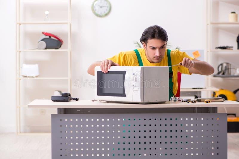 年轻安装工在服务中心的修理微波 免版税库存照片