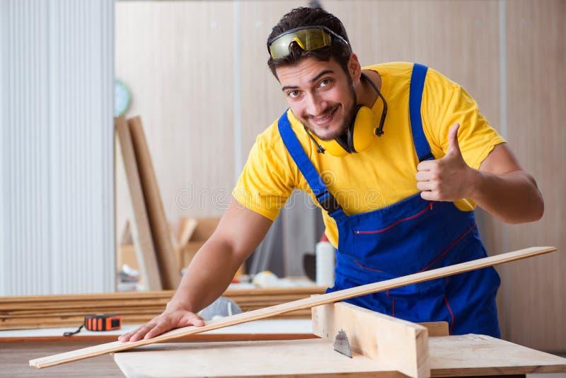年轻安装工木匠运作的切口木头 库存图片