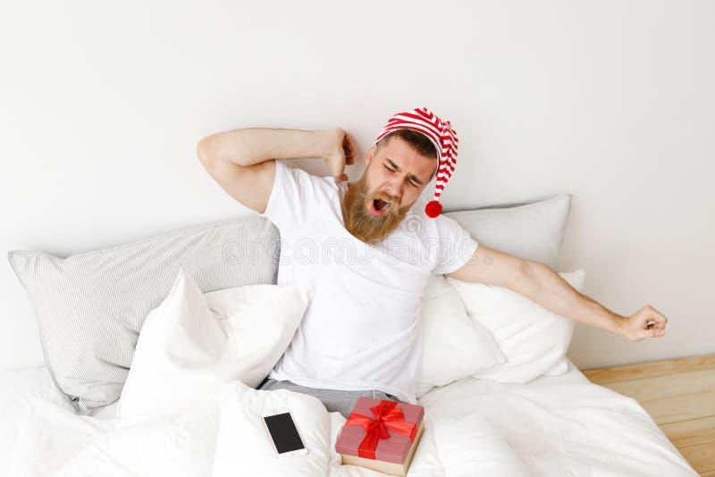 年轻宜人的看的男性在床上在舒适的床上舒展并且打呵欠,及早在上午醒,坐,被围拢 免版税库存图片