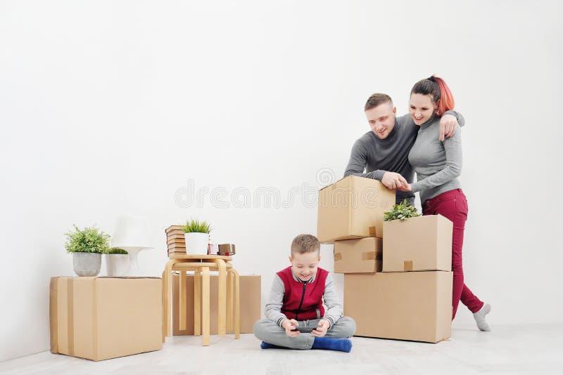 年轻家庭、人妇女和儿童儿子坐在新的公寓的地板 有货物的箱子在白色背景 免版税库存照片