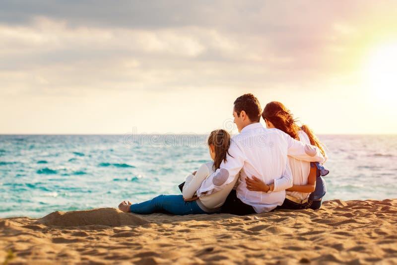 年轻家庭一起在黄昏太阳坐海滩 库存照片