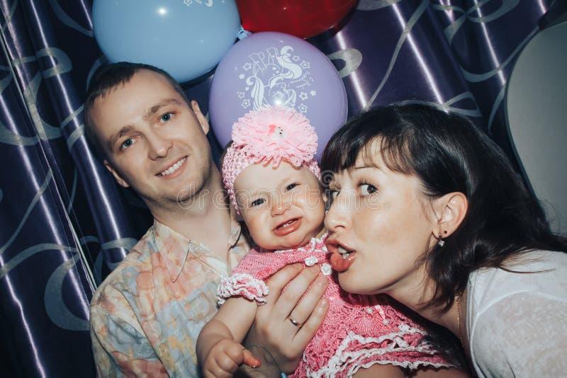 年轻家庭包括父亲、母亲和小女儿在屋子里 免版税库存图片