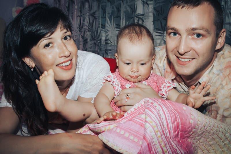 年轻家庭包括父亲、母亲和小女儿在屋子里 免版税图库摄影