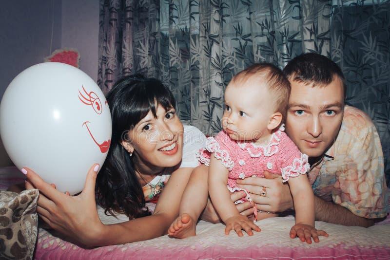 年轻家庭包括父亲、母亲和小女儿在屋子里 库存照片