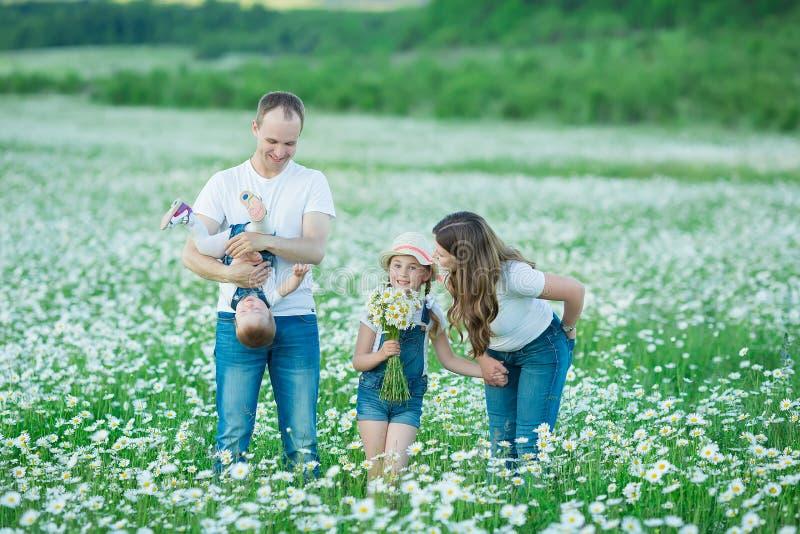 年轻家庭在花讲台春黄菊anjoy温泉生活领域愉快与在村庄土气行动的逗人喜爱的面孔一起 免版税库存图片