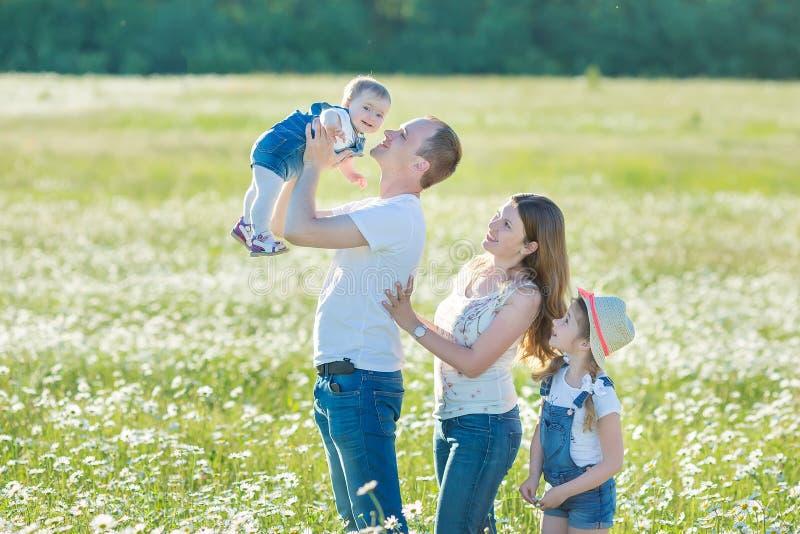 年轻家庭在花讲台春黄菊anjoy温泉生活领域愉快与在村庄土气行动的逗人喜爱的面孔一起 库存照片