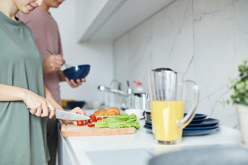 年轻家庭支持的厨房用桌和烹调早餐 免版税图库摄影