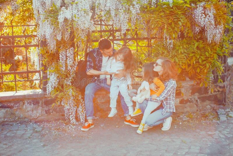 年轻家庭有休息在开花的树下 库存照片