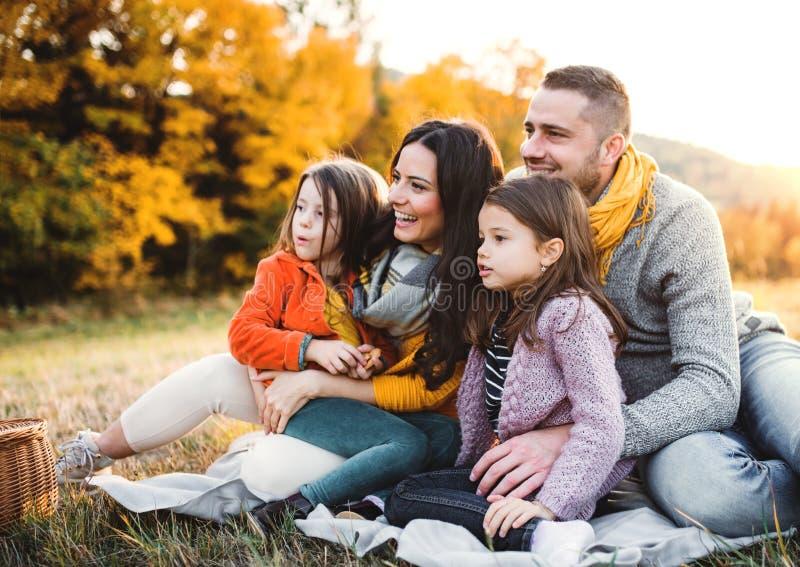 年轻家庭画象有两个小孩子的在日落的秋天自然的 库存照片