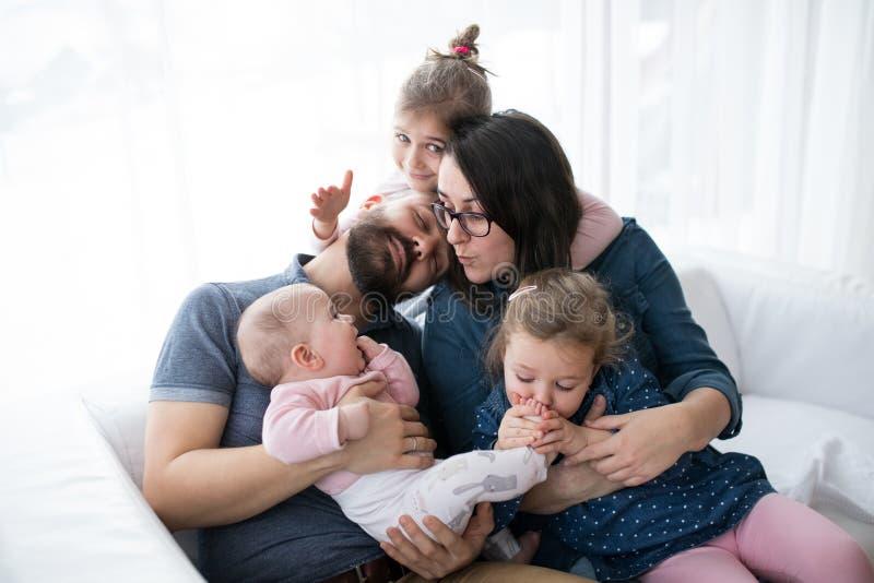 年轻家庭画象有小孩子的户内坐沙发,获得乐趣 免版税库存照片