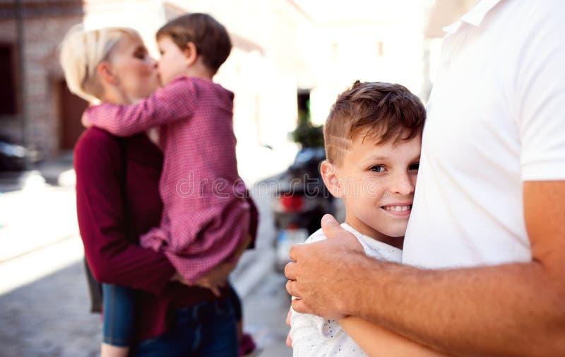 年轻家庭的中央部位有走户外在镇里的两个小孩子的 库存照片