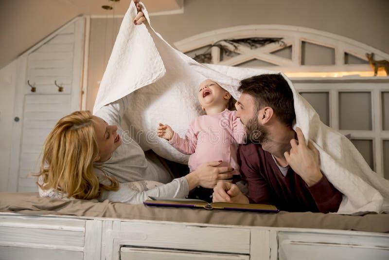 年轻家庭获得在床上的乐趣在卧室 免版税库存照片