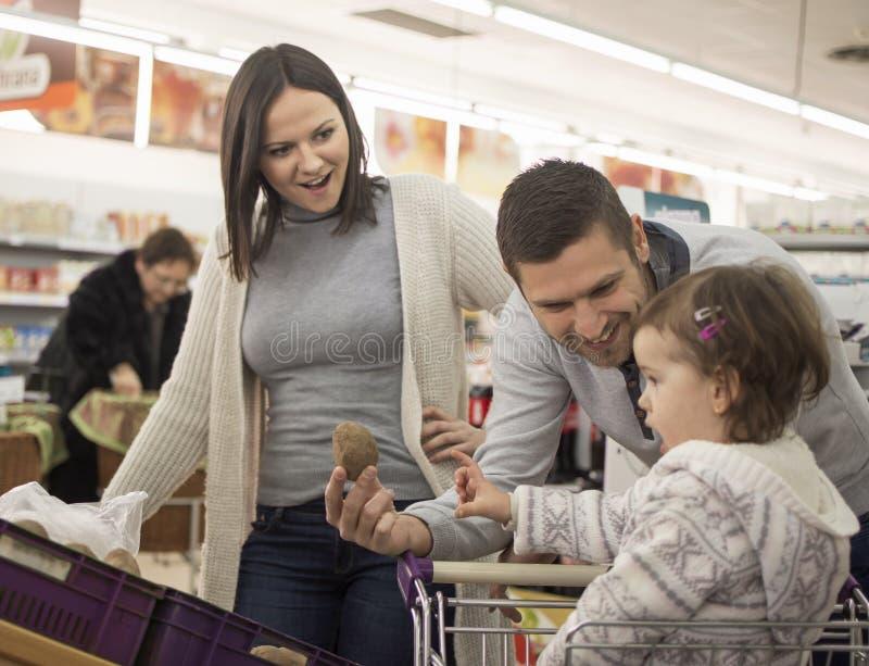 年轻家庭购买在超级市场 免版税库存照片