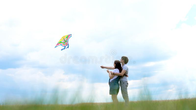 年轻家庭,执行风筝的夫妇蓝天和云彩 免版税图库摄影