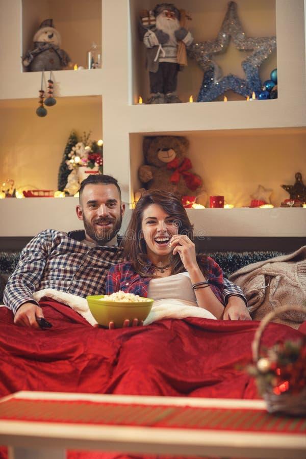 年轻对在吃玉米花的床上,当看电视时 免版税库存图片