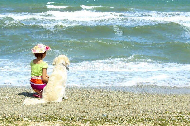 年轻小女孩和金毛猎犬狗坐海滩 免版税库存照片