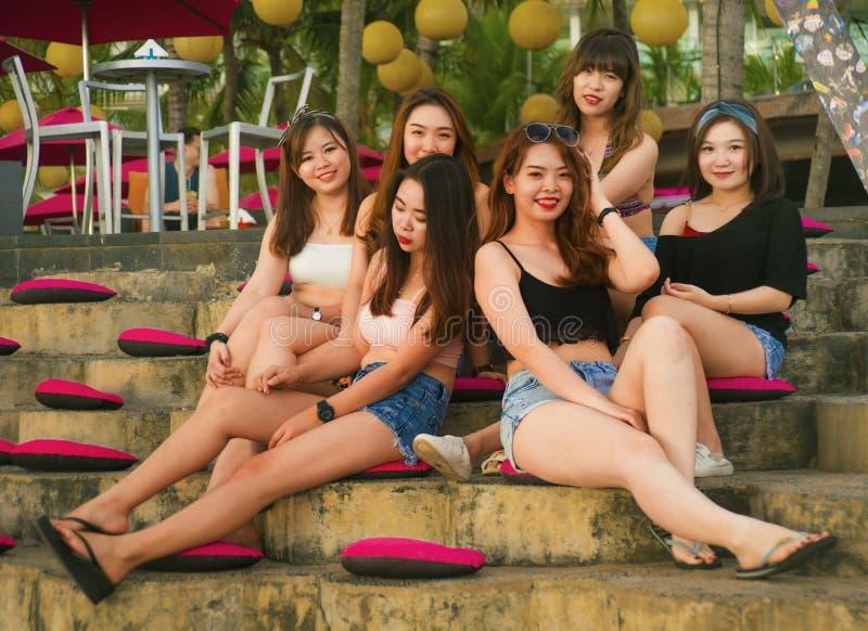 年轻小组愉快和美丽的亚裔中国女孩有有连贯性享用的假日在热带手段在朋友 库存照片