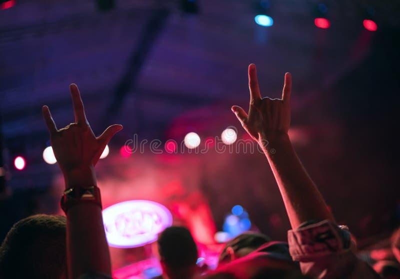 年轻少年女孩举了有支持在夜音乐会的垫铁姿态的标志的两只手喜爱的摇滚乐队 免版税库存照片