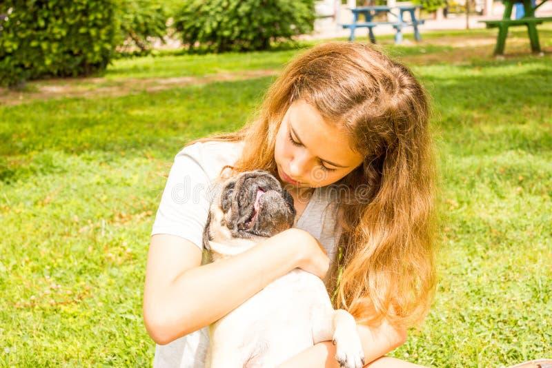 年轻少年女孩在绿草的公园拥抱她的哈巴狗狗 免版税库存图片