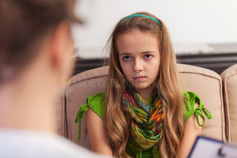 年轻少年女孩看与怀疑和不耐烦,坐在建议 免版税图库摄影