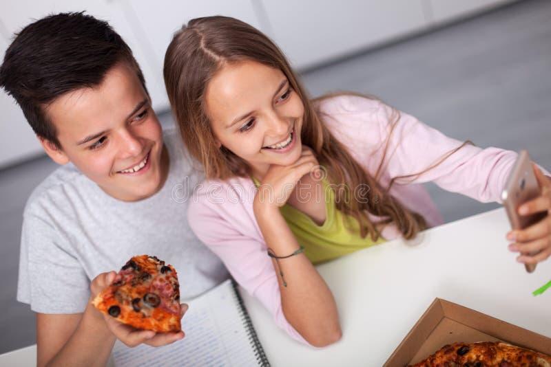 年轻少年男孩和女孩一起学习-吃薄饼 库存图片
