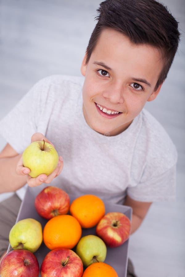 年轻少年男孩坐与果子板材的地板  免版税库存照片