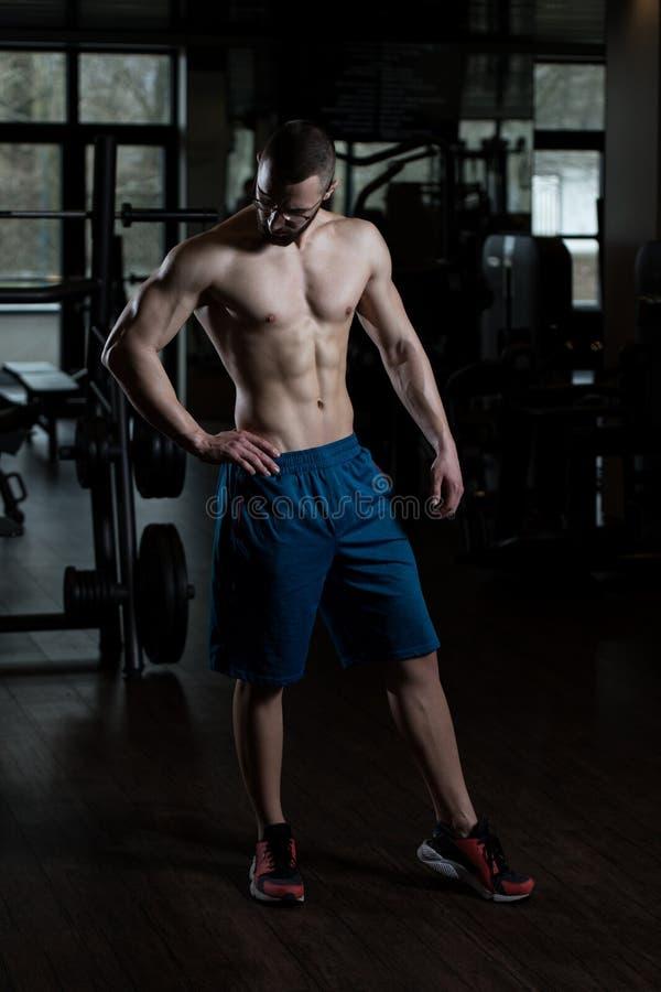 年轻屈曲肌肉的爱好健美者佩带的镜片 免版税库存图片