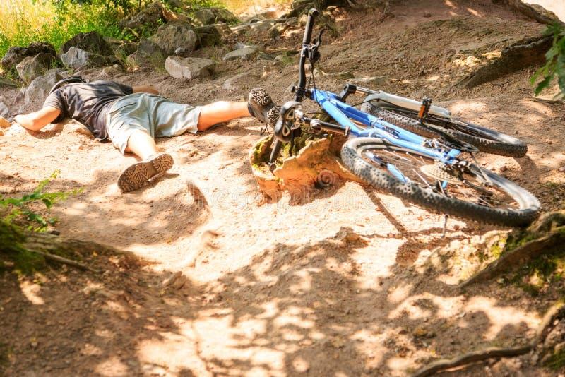 年轻山骑自行车的人跌下他的自行车 免版税库存图片