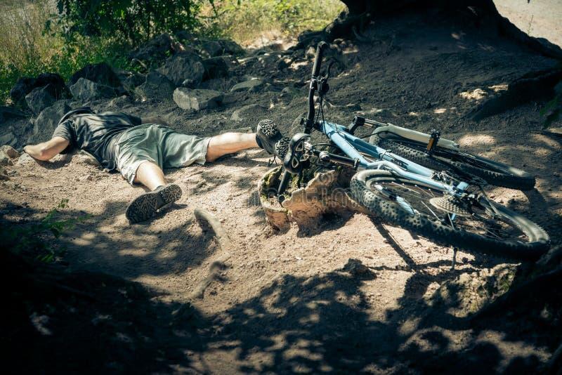 年轻山骑自行车的人跌下他的自行车 库存图片