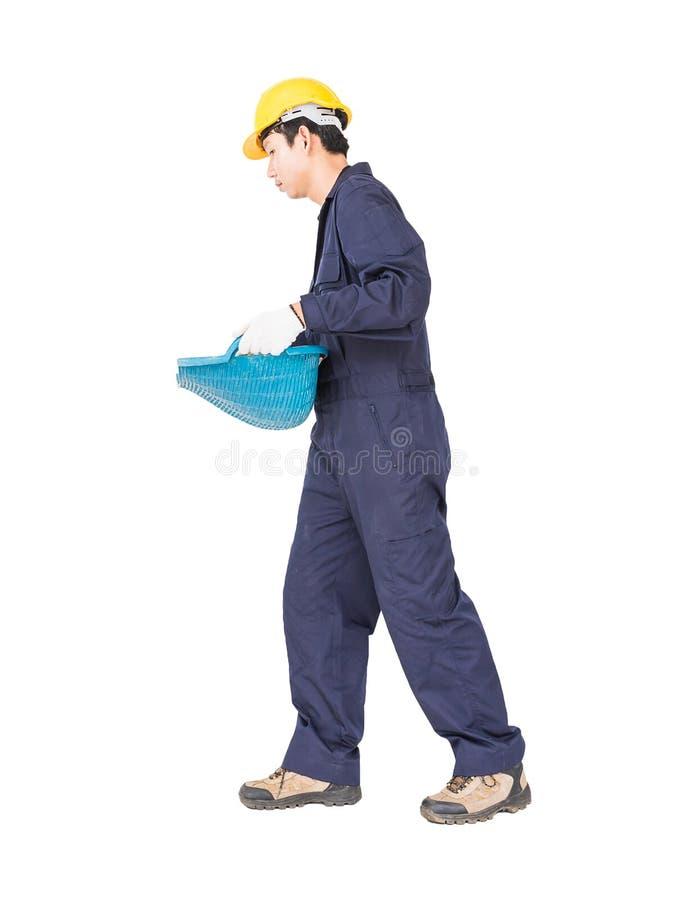 年轻工人举行煤斗或蛤壳状机件塑造了篮子 免版税库存图片