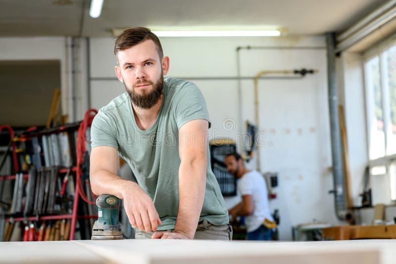 年轻工人在木匠车间 免版税库存照片