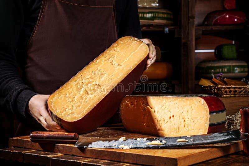 年轻工人藏品一半轮子gauda乳酪在商店 木背景,乳酪的刀子 关闭视图 复制文本的空间 免版税库存图片