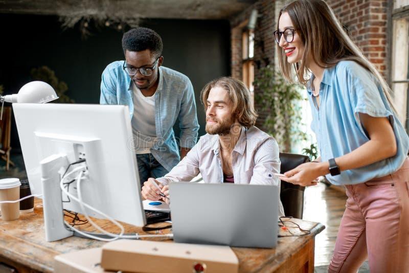 年轻工友与计算机一起使用户内 免版税库存图片