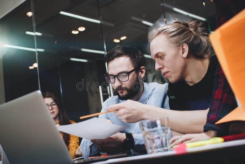年轻工程学学生队研究一个新的项目,谈论在纸和膝上型计算机用图解法表示 库存照片
