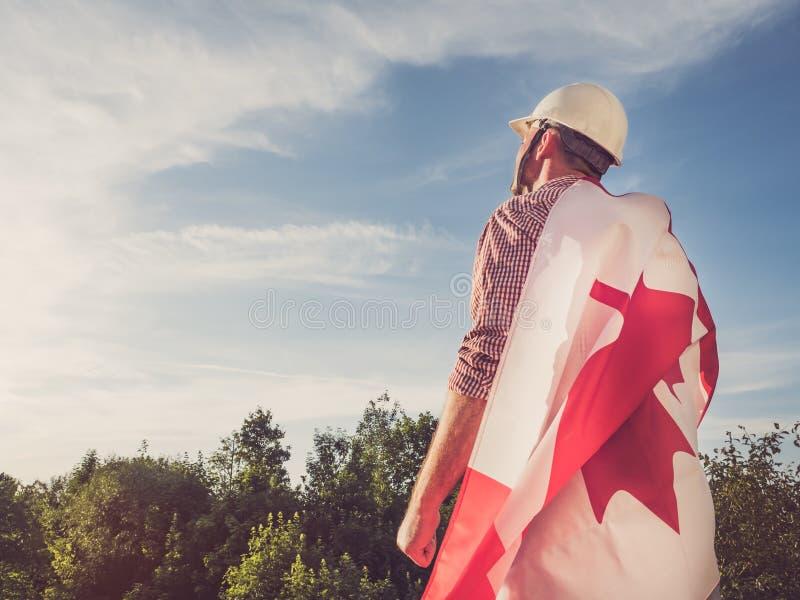 年轻工程师、白色安全帽和加拿大旗子 库存照片