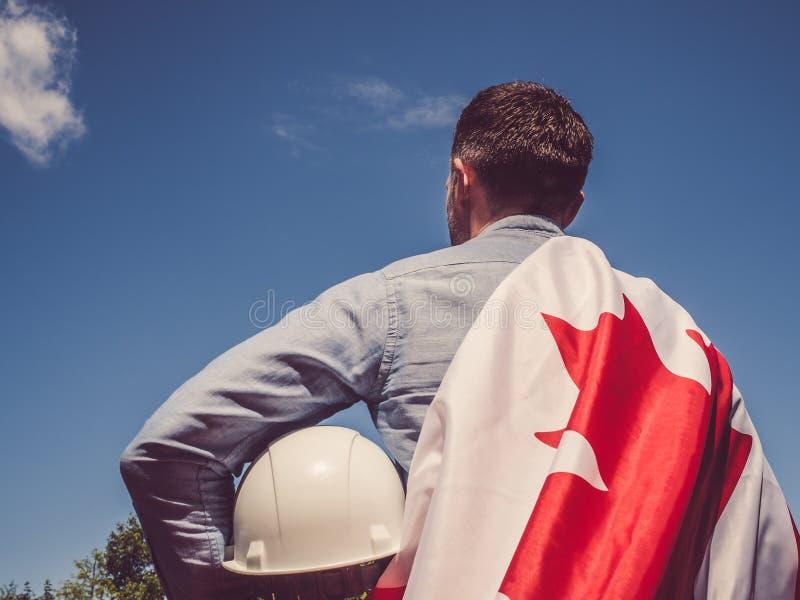 年轻工程师、白色安全帽和加拿大旗子 库存图片