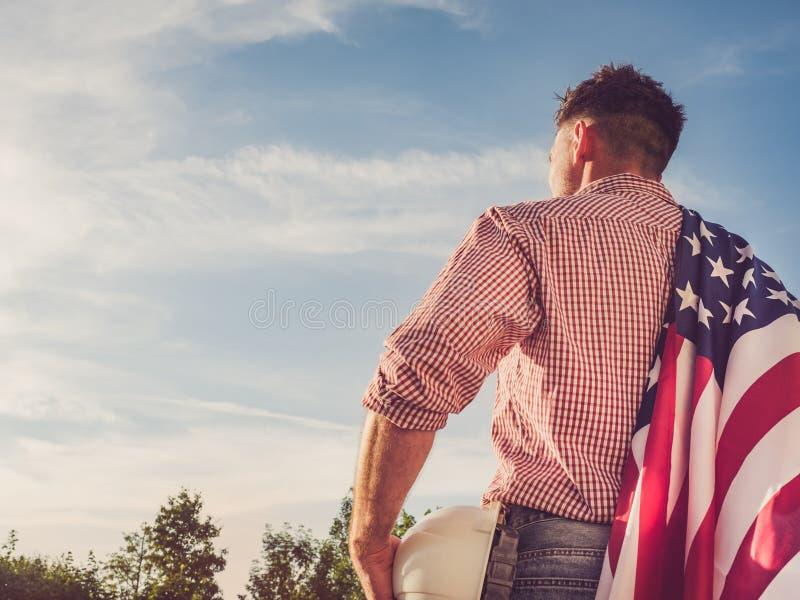 年轻工程师、白色安全帽和美国国旗 库存图片