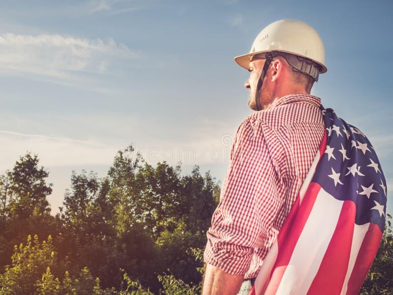 年轻工程师、白色安全帽和美国国旗 免版税图库摄影