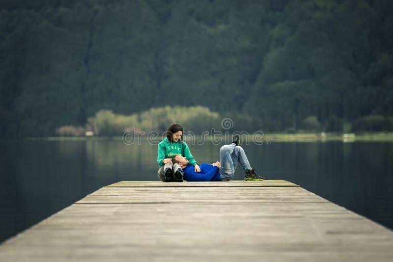 年轻已婚夫妇坐码头由火山的湖 库存图片