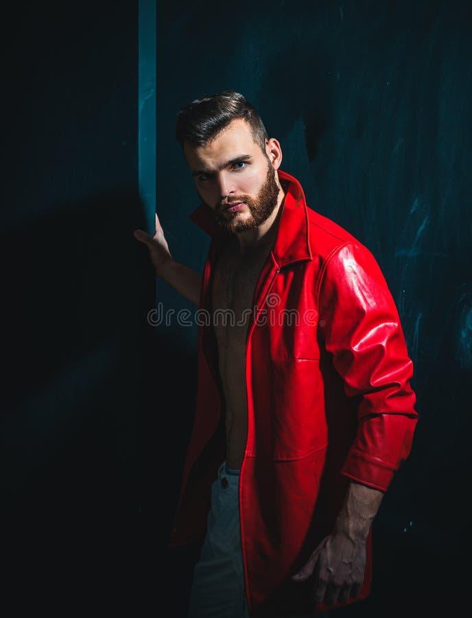 年轻帅哥画象  穿在赤裸肌肉躯干的帅哥红色皮夹克在黑暗的背景 免版税库存照片